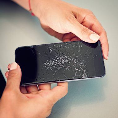 woman holding broken iphone